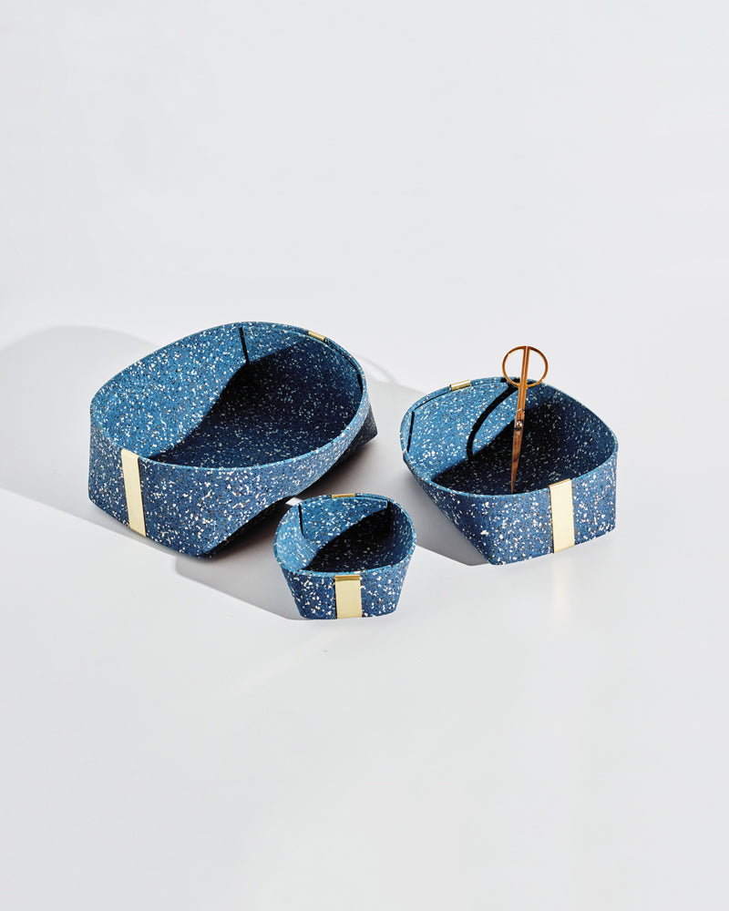 Three speckled blue rubber and brass baskets on white background. One basket has brass scissors inside.