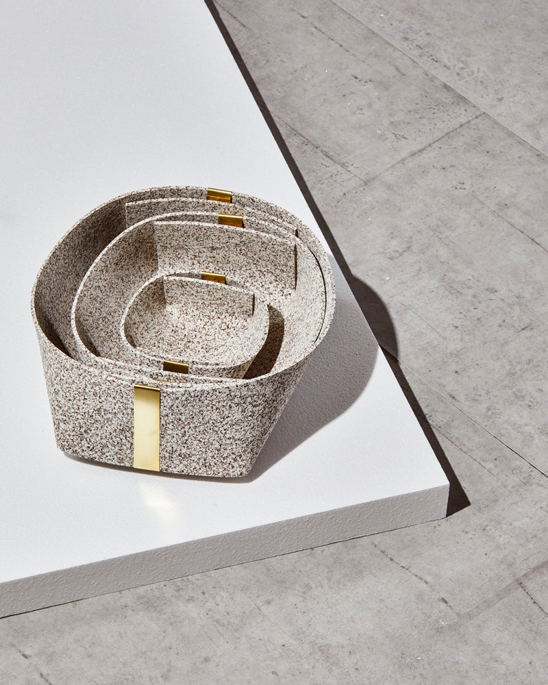 Three speckled beige rubber and brass baskets, nested inside one another on white foam board on concrete surface