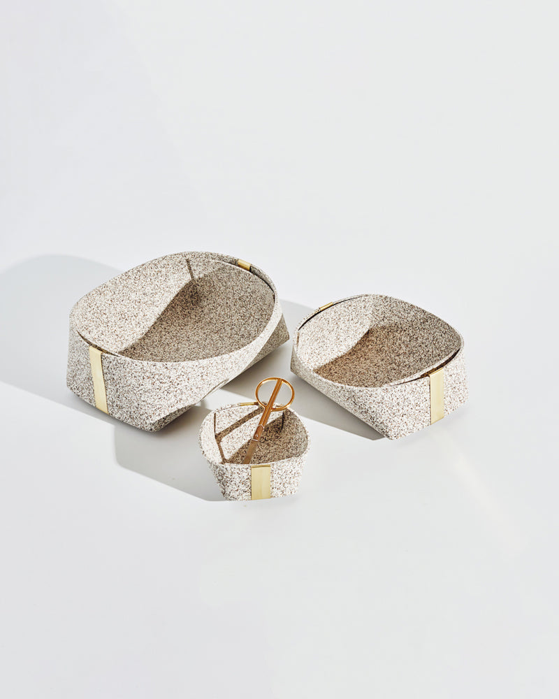 Three speckled beige rubber and brass baskets on white background. One basket has brass scissors inside.