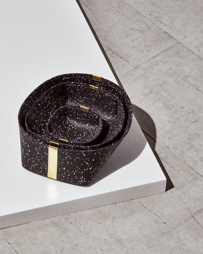 Three speckled black rubber and brass baskets, nested inside one another on white foam board on concrete surface