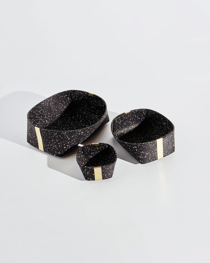 Three speckled black rubber and brass baskets on white background.