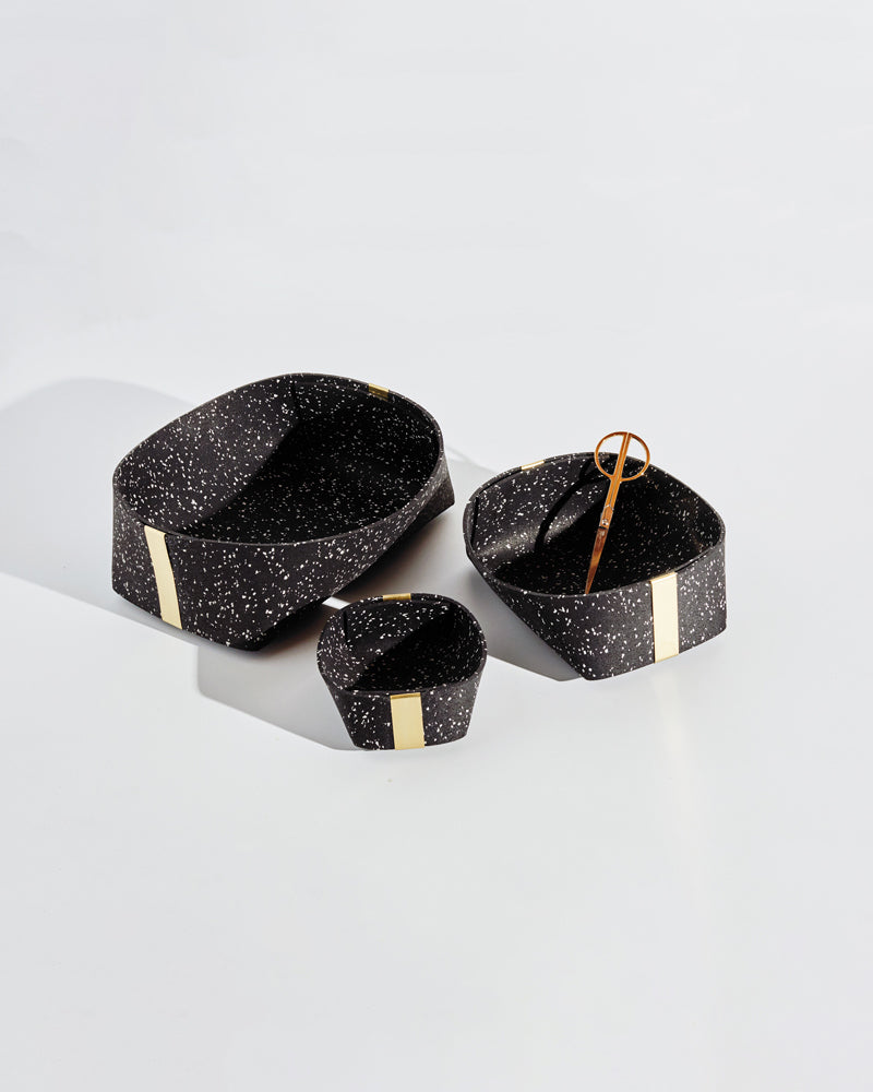 Three speckled black rubber and brass baskets on white background. One basket has brass scissors inside.