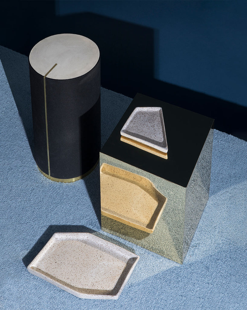 Ceramic nesting tray on shiny brass rectangular side table. Round black rubber side table with brass strip, brass base and gray concrete table top on blue carpet.