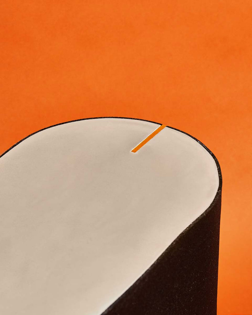 Detail image of val black rubber side table with with brass strip on orange background.