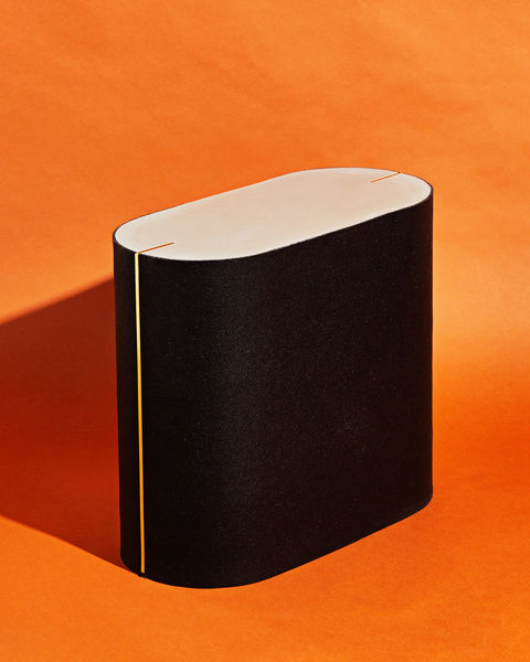 Oval black rubber side table with with brass strips on orange background.