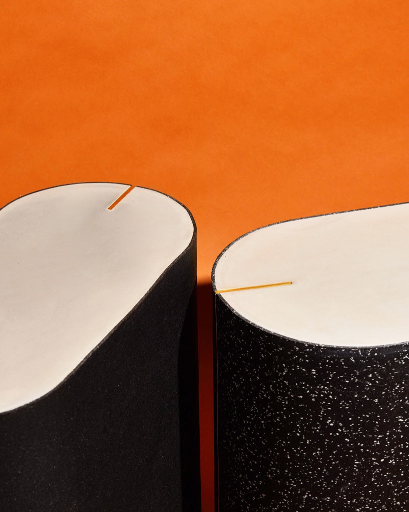 Detail image of black rubber and speckled black rubber oval side tables on orange background.