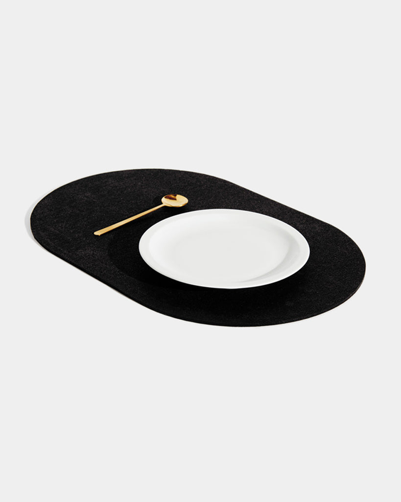 Angled view of black rubber capsule placemat with white plate and brass spoon on white background.
