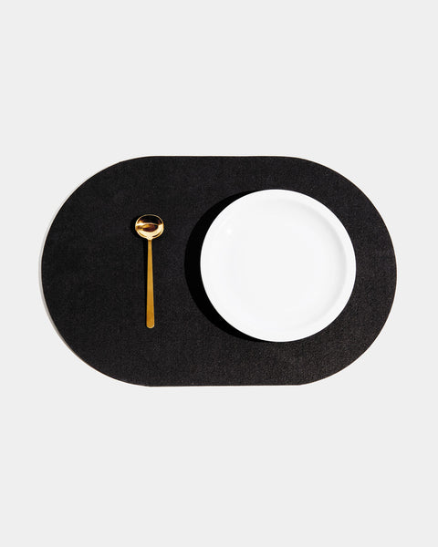 Top view of black rubber capsule placemat with white plate and brass spoon on white background.