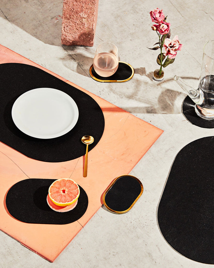 Spring table setting with black rubber capsule placemats, capsule trivets and brass ring coaster. The setting is styled with grapefruit, pink liquid in glass and pink flower.