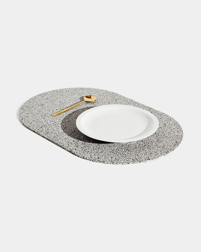 Angled view of speckled grey rubber capsule placemat with white plate and brass spoon on white background.