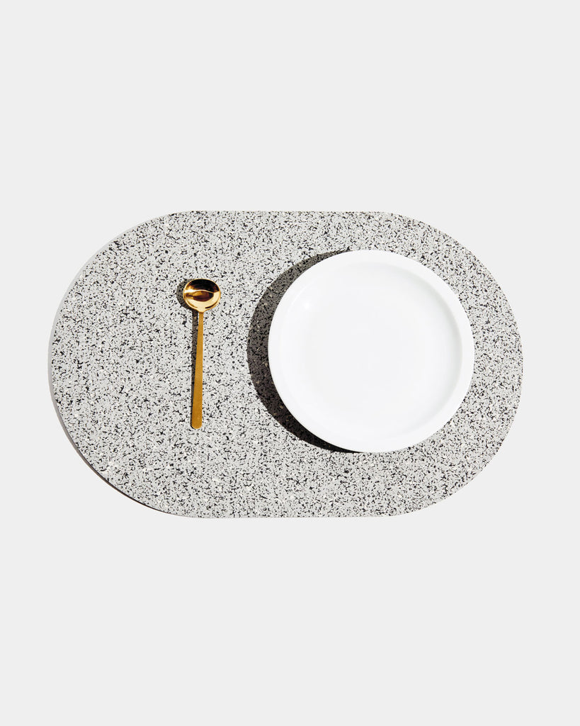 Top view of speckled grey rubber capsule placemat with white plate and brass spoon on white background.