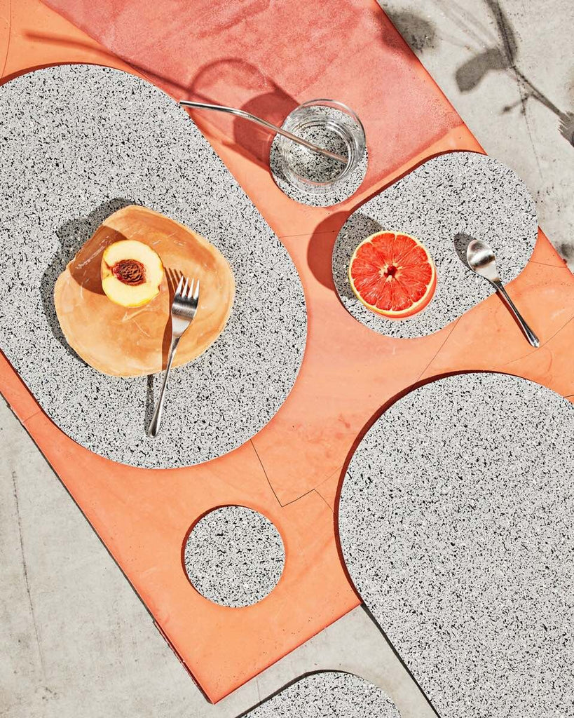 Spring table setting with speckled grey rubber capsule placemats, capsule trivets and round coasters on concrete and terracotta surface. The setting is styled with half cut grapefruit, peach, spoon, fork and a glass of water with metallic straw.