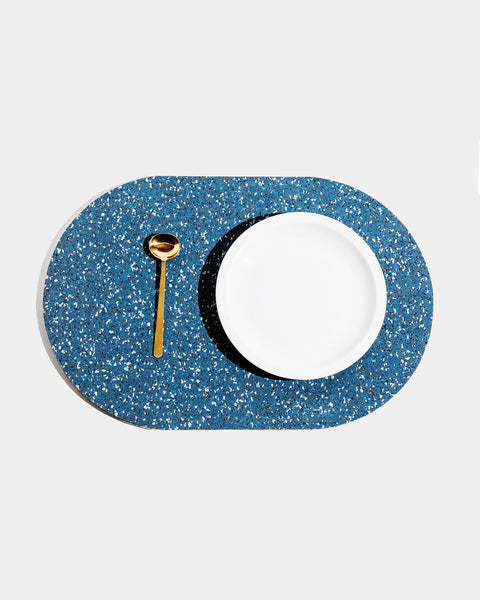 Top view of speckled blue rubber capsule placemat with white plate and brass spoon on white background.
