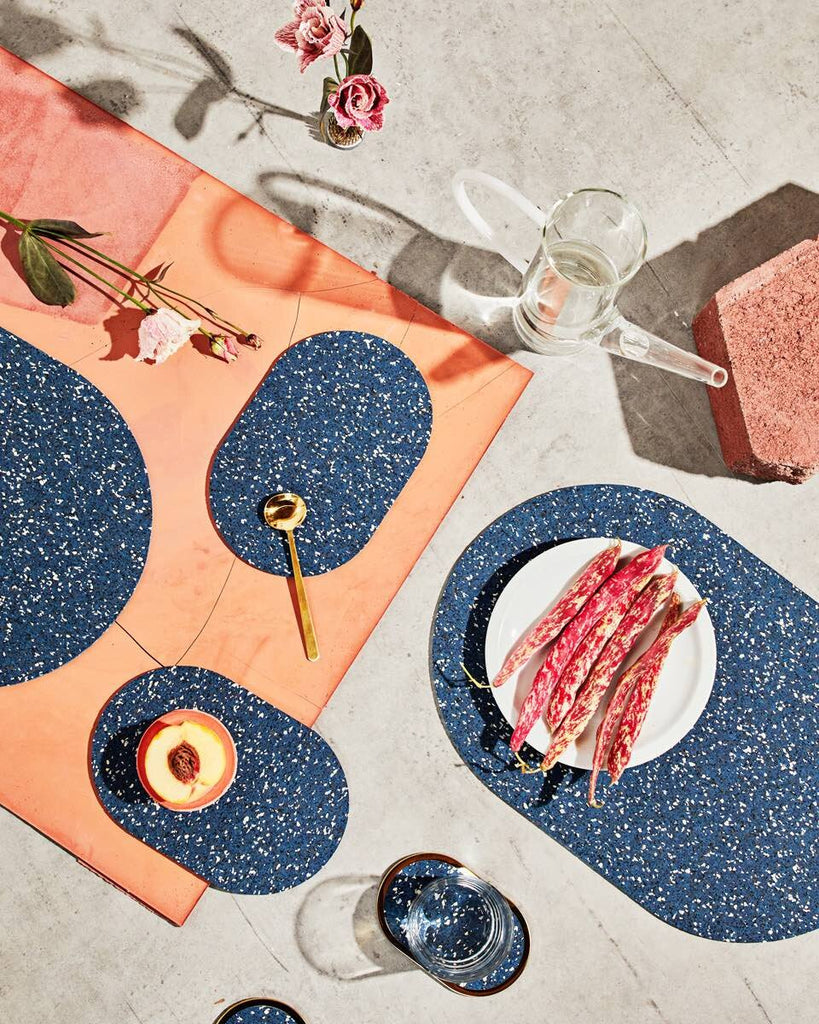 Spring table setting with speckled blue rubber capsule placemats, capsule trivets and brass ring coasters on concrete and terracotta surface. The setting is styled with cut half peach, brass spoon, water pitcher, glass and pink flowers.
