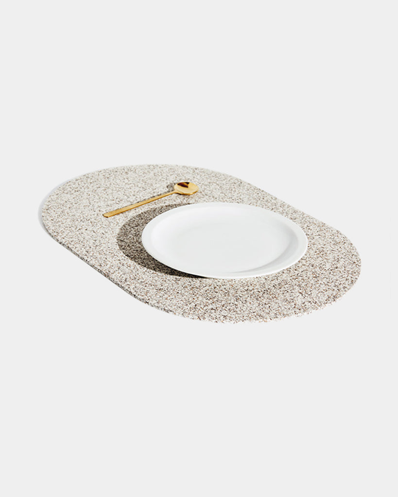 Angled view of speckled beige rubber capsule placemat with white plate and brass spoon on white background.