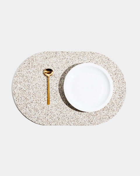 Top view of speckled beige rubber capsule placemat with white plate and brass spoon on white background.