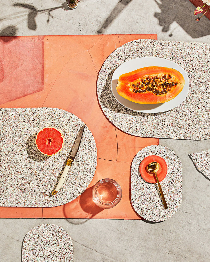 Spring table setting with speckled beige rubber capsule placemats and capsule trivets on concrete and terracotta surface. The setting is styled with cut half grapefruit, papaya, brass spoon, glass of water and knife.