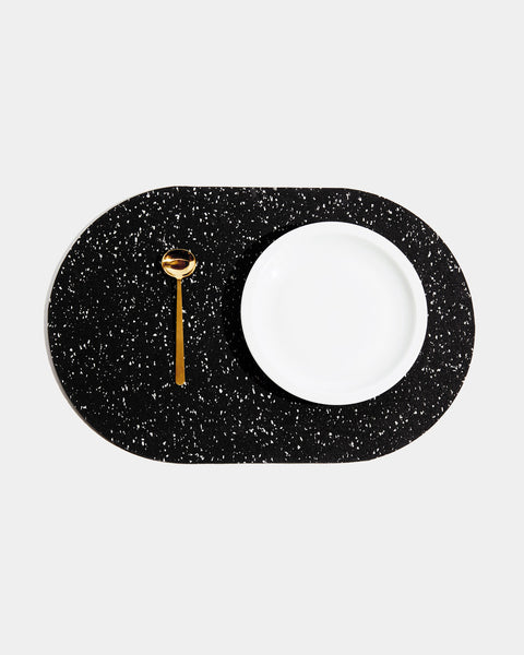 Top view of speckled black rubber capsule placemat with white plate and brass spoon on white background.