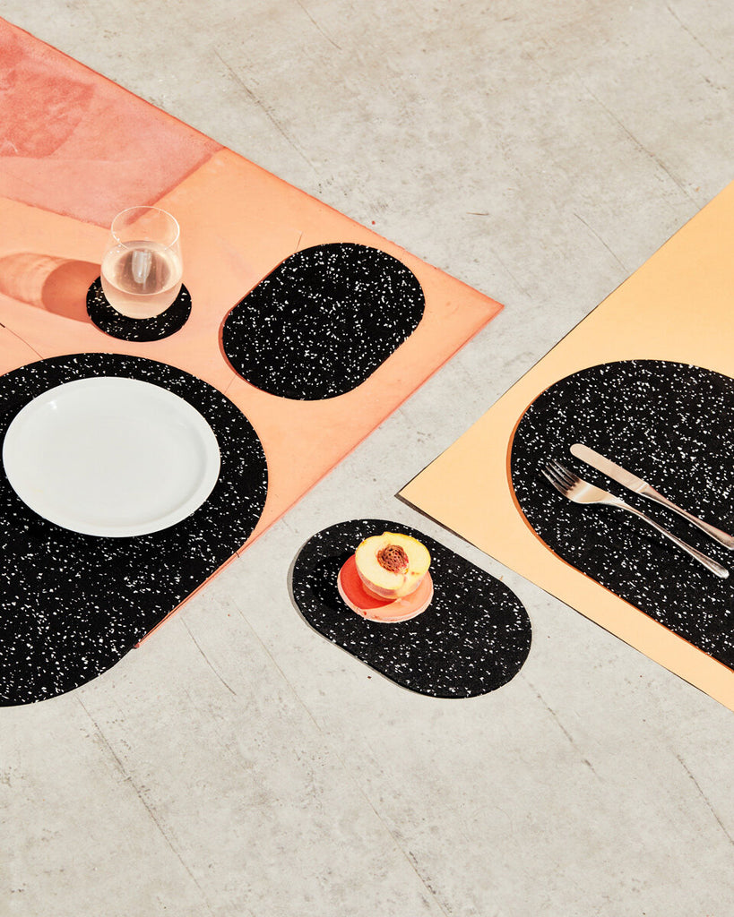Spring table setting with speckled black rubber capsule placemats and capsule trivets on concrete and terracotta surface. The setting is styled with cut half peach, white plate, glass and cutlery.