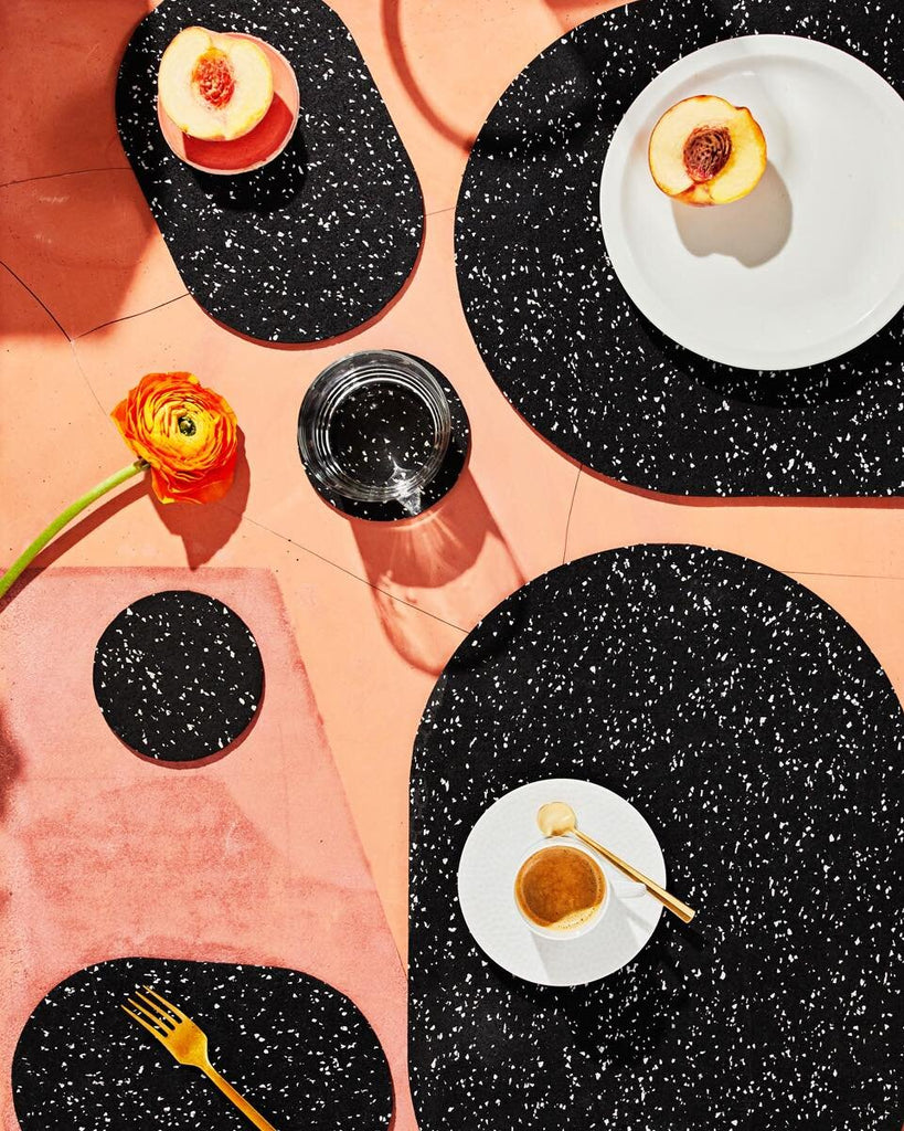 Spring table setting with speckled black rubber capsule placemats and capsule trivets on terracotta surface. The setting is styled with peach, espresso, glass of water, brass fork and orange flower.
