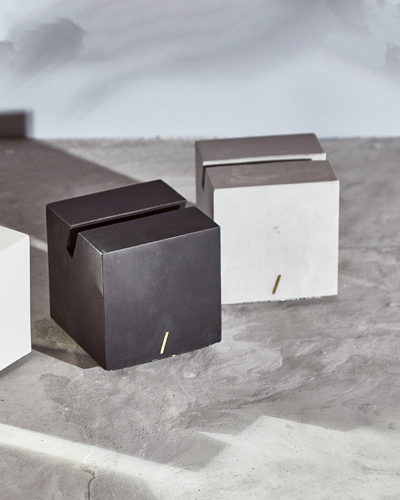 Black and gray cube card holders on concrete surface.