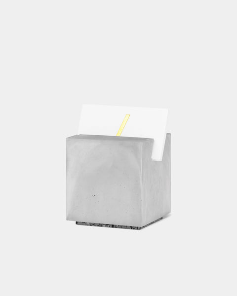 Gray cube card holder with white business card front angle view.