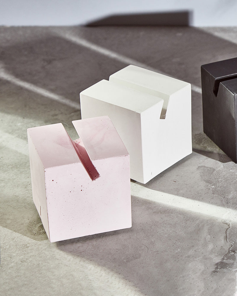 White and pink cube card holders on concrete surface.