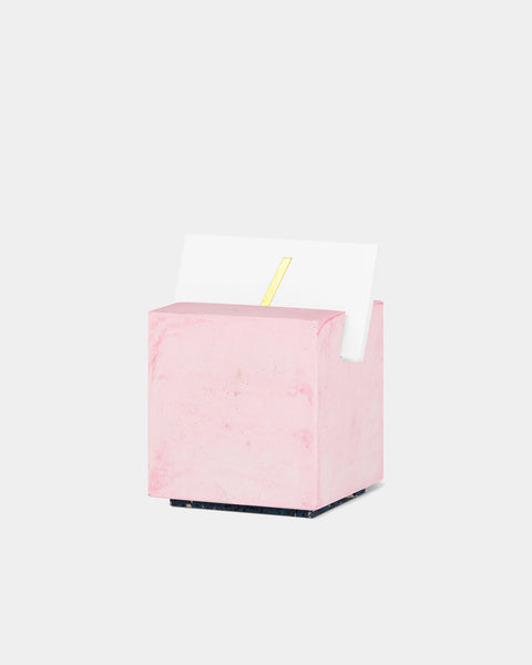 Pink cube card holder with white business card front angle view.