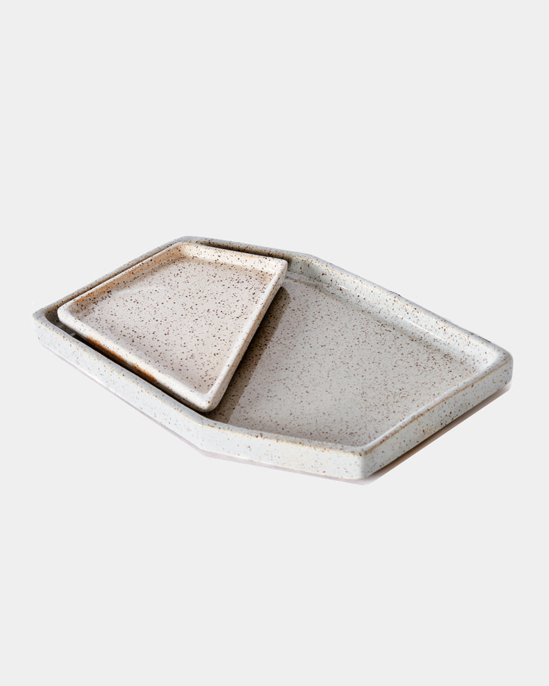 Glossy gray and speckled white ceramic nesting tray on white background.