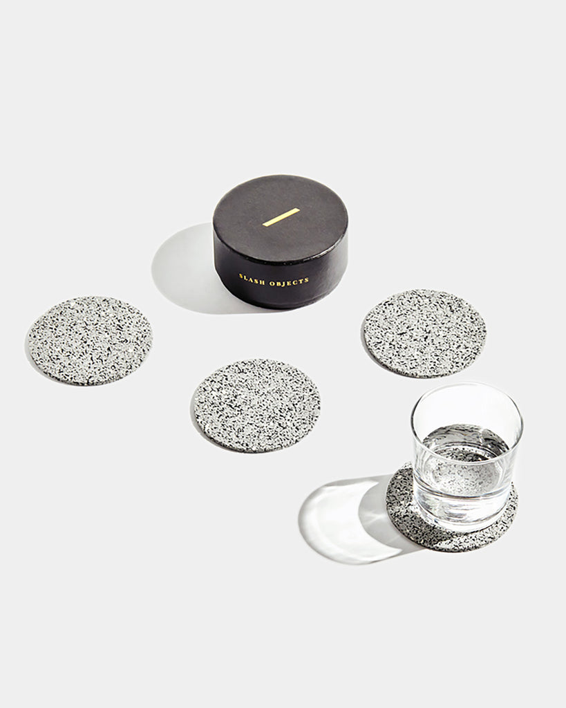 Four speckled grey round rubber coasters and round black coaster box on white surface. One coaster contains glass filled with water.