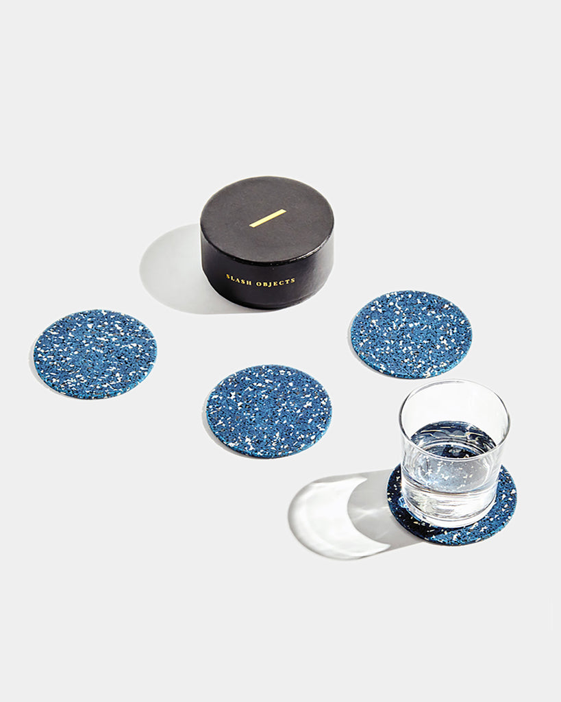 Four speckled blue round rubber coasters and round black coaster box on white surface. One coaster contains glass filled with water.