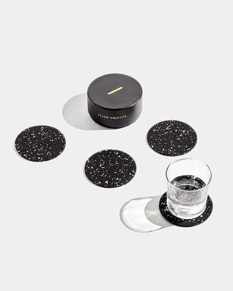 Four speckled black round rubber coasters and round black coaster box on white surface. One coaster contains glass filled with water.