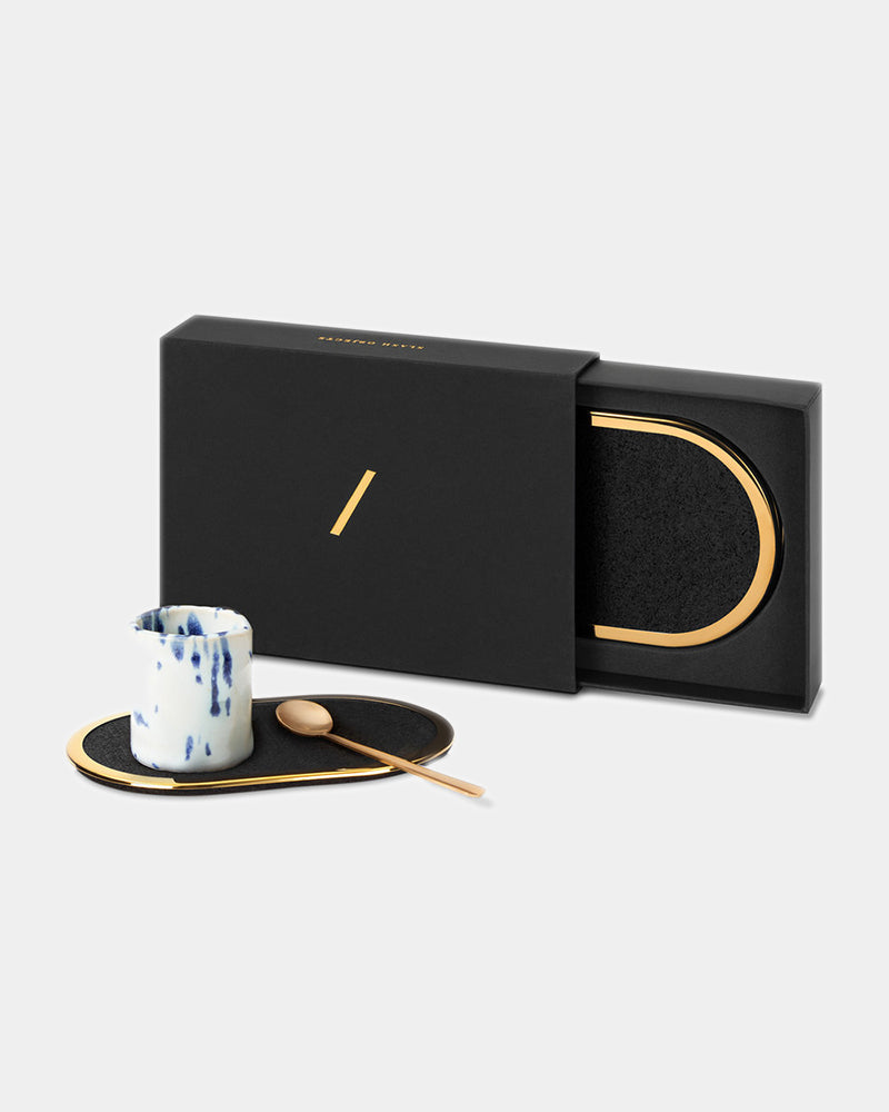 Oval brass ring black rubber coaster with espresso cup and brass spoon. Oval brass ring black rubber coaster inside black rectangular packaging.