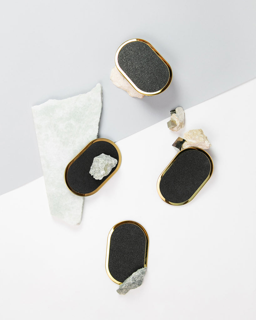 Four oval brass ring black rubber coasters styled with rocks and marble.