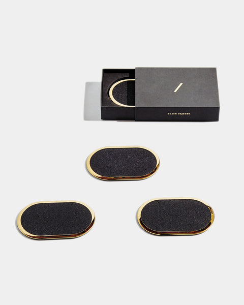 Four brass oval ring black rubber coasters on white surface. One of the coasters has glass filled with water. One coaster is inside black rectangular packaging.