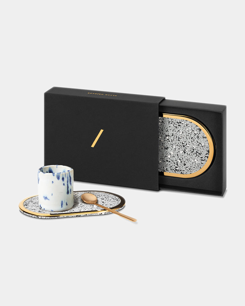 Oval brass ring speckled grey rubber coaster with espresso cup and brass spoon. Oval brass ring black rubber coaster inside black rectangular packaging.