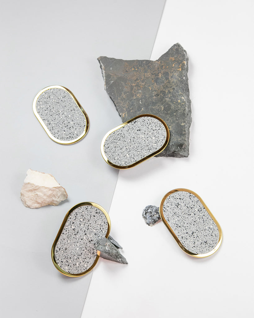 Four oval brass ring speckled grey rubber coasters styled with rocks and marble.