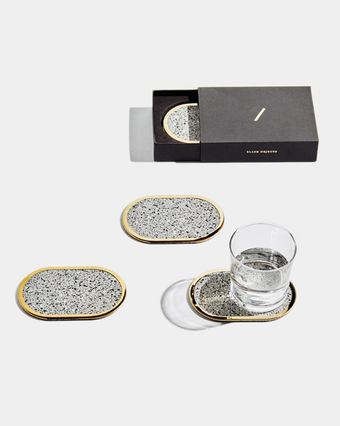 Four brass oval ring grey speckled rubber coasters on white surface. One of the coasters has glass filled with water. One coaster is inside black rectangular packaging.