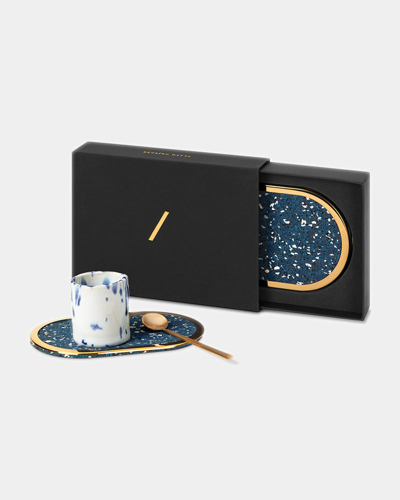 Oval brass ring speckled blue rubber coaster with espresso cup and brass spoon. Oval brass ring black rubber coaster inside black rectangular packaging.