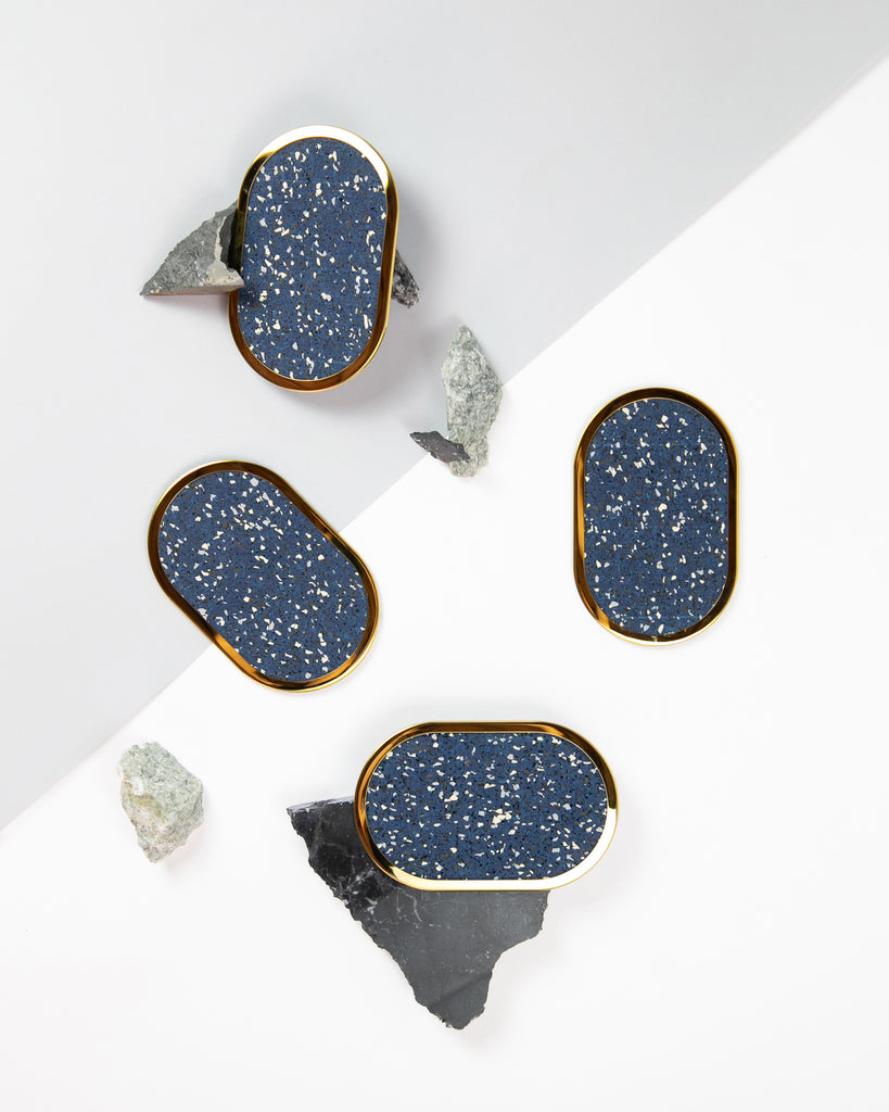 Four oval brass ring speckled blue rubber coasters styled with rocks and marble.