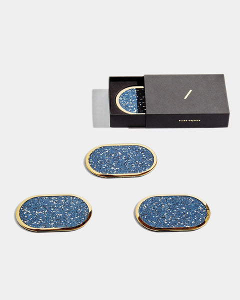 Four brass oval ring blue speckled rubber coasters on white surface. One of the coasters has glass filled with water. One coaster is inside black rectangular packaging