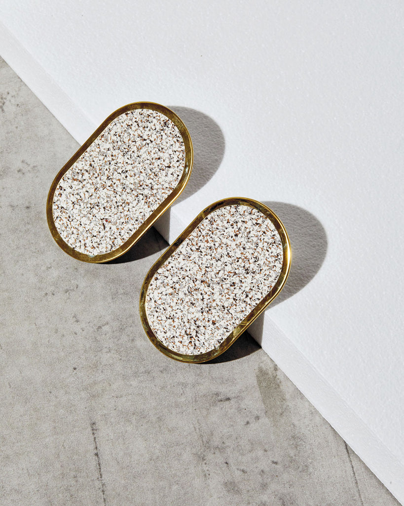 Two brass oval ring beige speckled rubber coasters on concrete surface leaned on white foam board.
