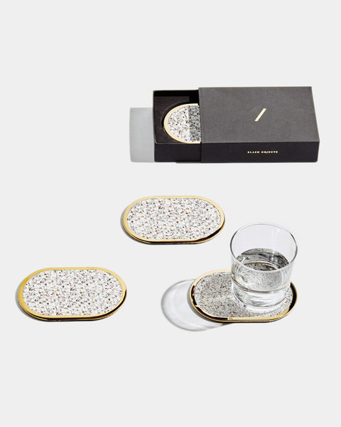 Four brass oval ring beige speckled rubber coasters on white surface. One of the coasters has glass filled with water. One coaster is inside black rectangular packaging.