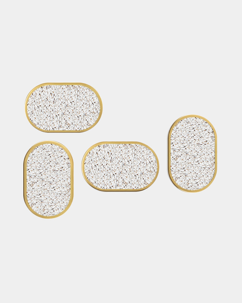Four brass oval ring beige speckled rubber coasters on white surface.