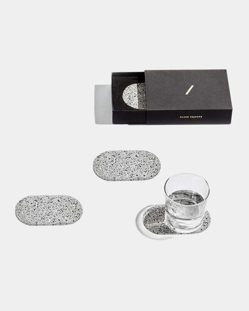 Four speckled grey oval rubber coasters on white surface. One of the coasters has glass filled with water. One coaster is inside black rectangular packaging.