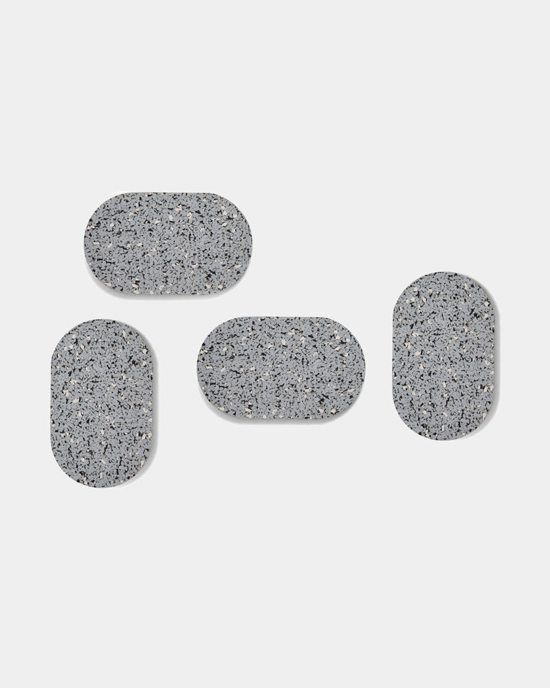 Four speckled grey oval rubber coasters on white surface.