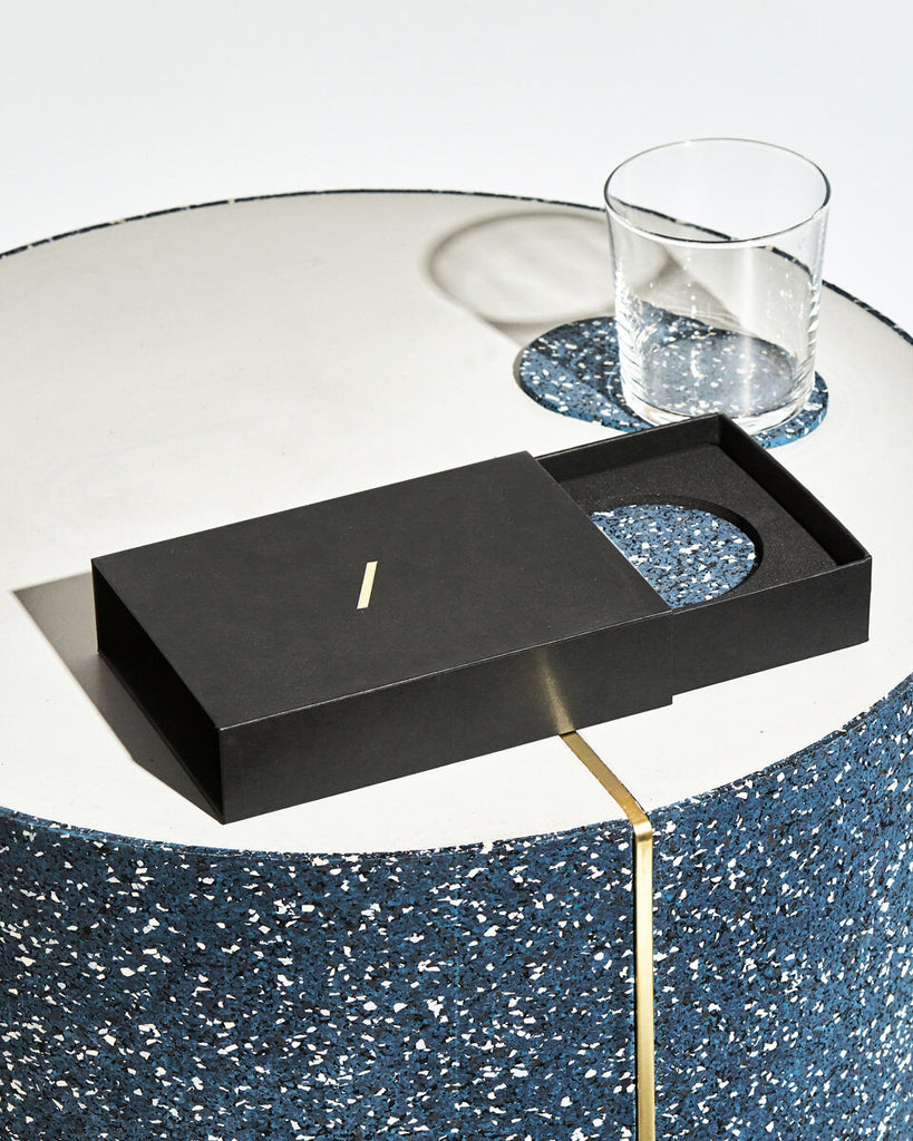 Speckled blue oval rubber coaster inside black rectangular packaging on concrete surface. Oval coaster with empty glass behind the packaging.