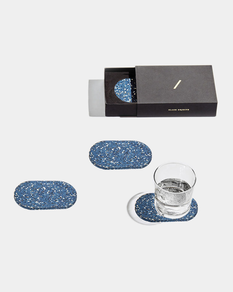 Four speckled blue oval rubber coasters on white surface. One of the coasters has glass filled with water. One coaster is inside black rectangular packaging.