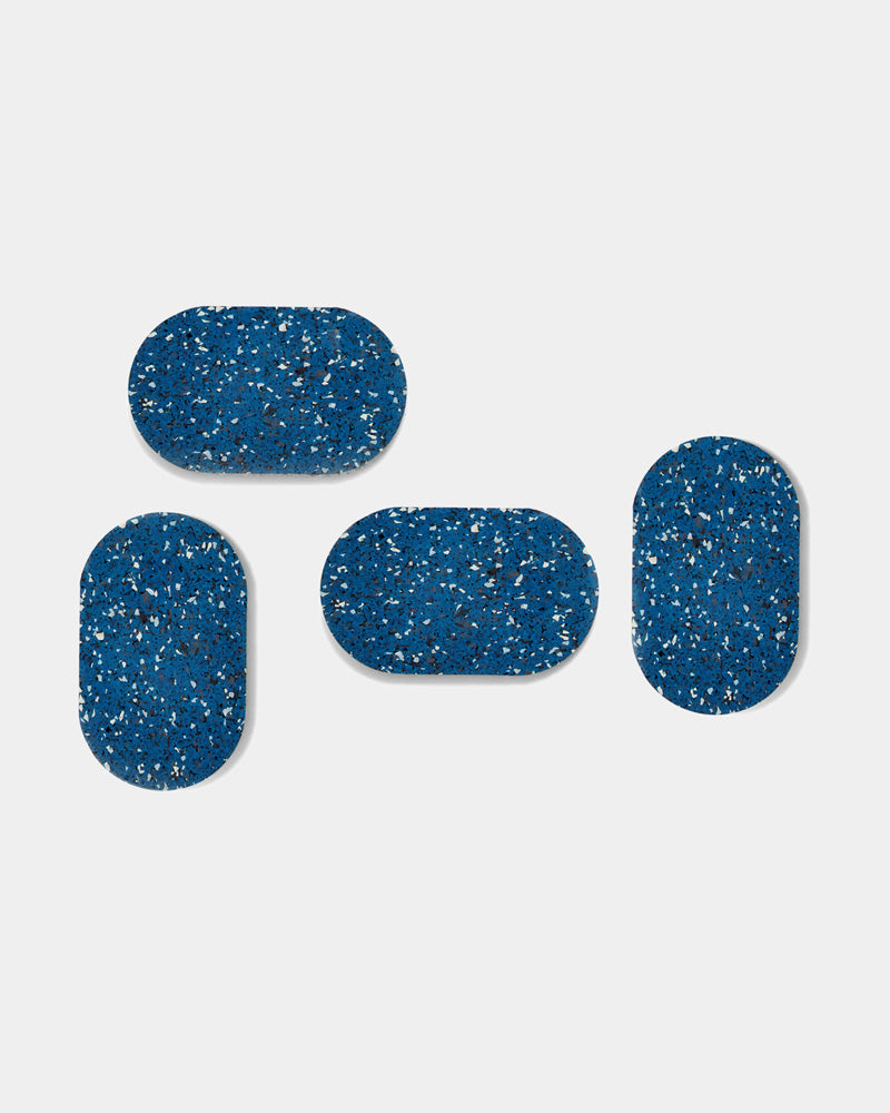 Four speckled blue oval rubber coasters on white surface.