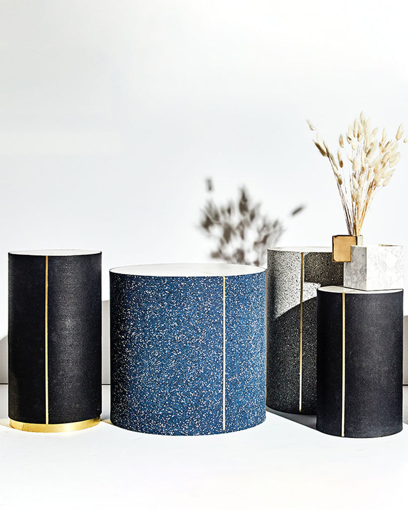 Four round side tables in speckled black, speckled gray, speckled blue and black rubber with brass strip and concrete table top.